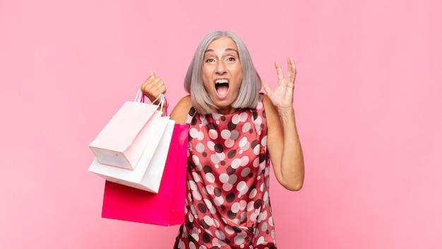 중년 여성이 공중에서 손을 들고 비명을 지르며 분노하고 좌절감을 느끼고 스트레스를 받고 쇼핑백으로 화가납니다.
