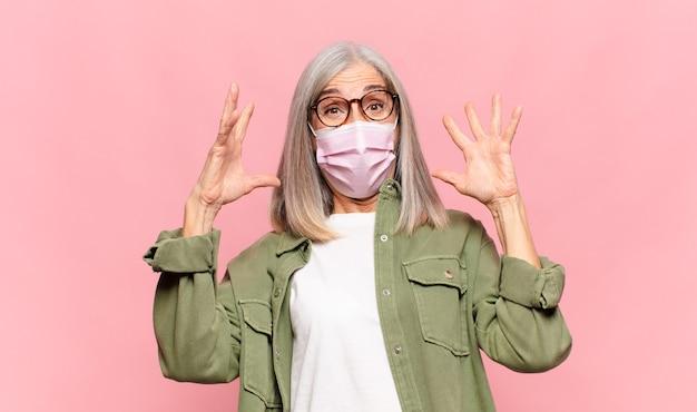 Женщина среднего возраста кричит с поднятыми руками, чувствуя ярость, разочарование, стресс и расстройство