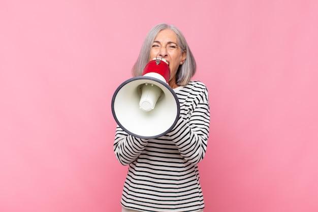 Женщина среднего возраста агрессивно кричит, выглядит очень рассерженной, расстроенной, возмущенной или раздраженной, кричит
