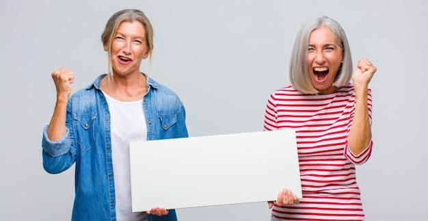 Женщина среднего возраста агрессивно кричит с гневным выражением лица или со сжатыми кулаками, празднуя успех
