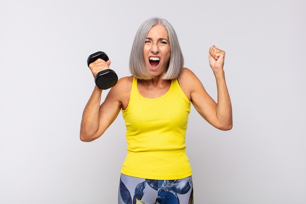Middle age woman shouting aggressively with an angry expression or with fists clenched celebrating success. fitness concept