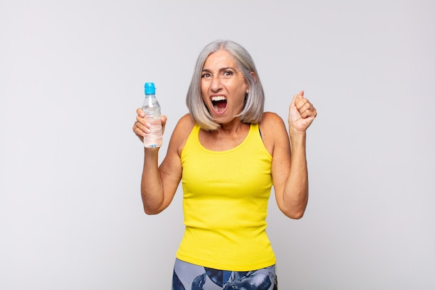 Middle age woman shouting aggressively with an angry expression or with fists clenched celebrating success