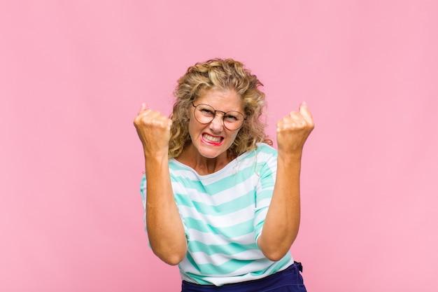 Женщина среднего возраста триумфально кричит, смеется и чувствует себя счастливой и взволнованной, празднуя успех
