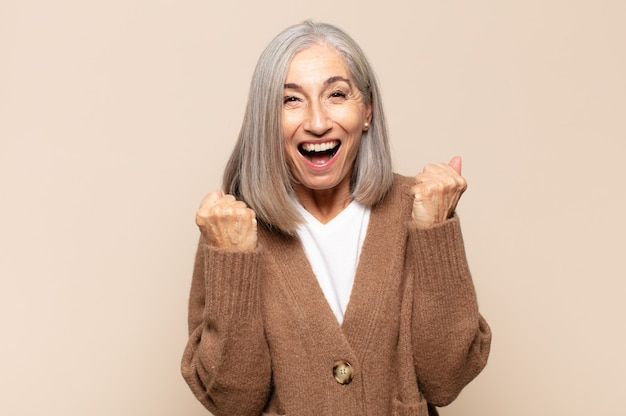 Middle age woman shouting triumphantly, laughing and feeling happy and excited while celebrating success
