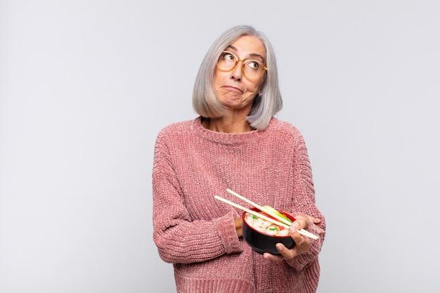 중년 여성이 어깨를 으쓱하고 혼란스럽고 불확실한 느낌, 팔로 의심하고 의아해 보이는 아시아 음식 개념