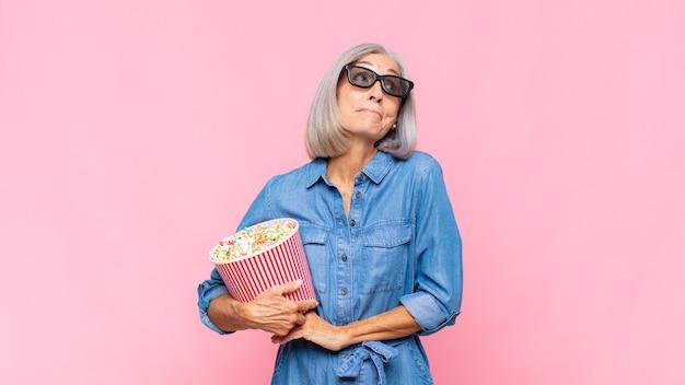 肩をすくめる中年の女性、混乱して不安を感じ、腕を組んで困惑しているように見える映画のコンセプト