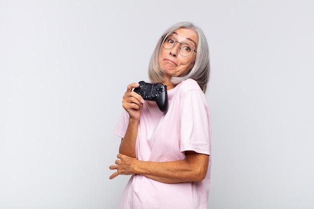 中年の女性は肩をすくめ、混乱し、不安を感じ、腕を組んで困惑した表情で疑っています。ゲーム機のコンセプト