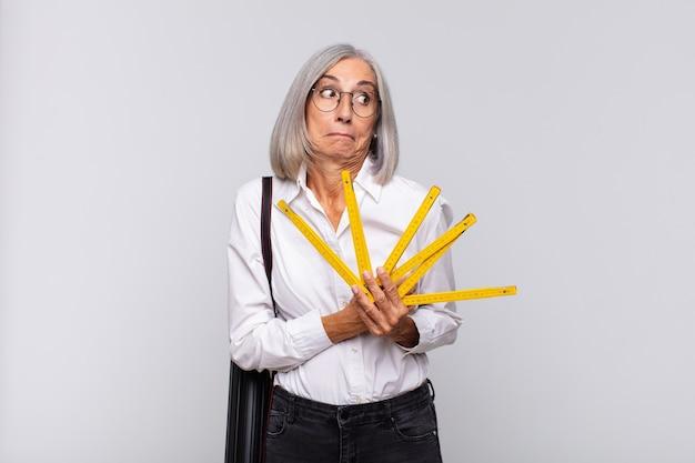 Женщина среднего возраста пожимает плечами, чувствуя себя смущенной и неуверенной изолированной