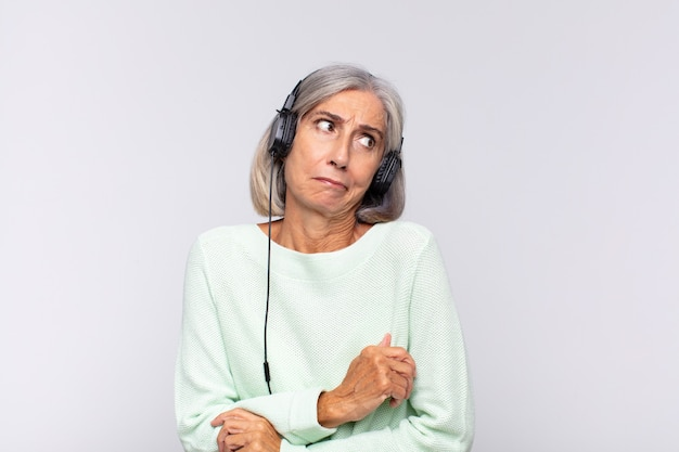 Middle age woman shrugging, feeling confused and uncertain, doubting with arms crossed and puzzled look