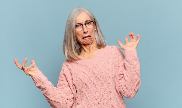 愚かで、狂った、混乱した、困惑した表情で肩をすくめる中年の女性、イライラして無知な感じ