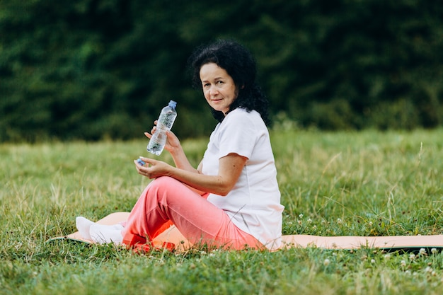 Middle age woman sitting in the yoga mat and holding a bottle with water.