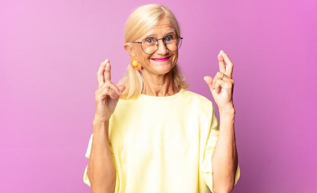 Женщина среднего возраста улыбается и тревожно скрещивает пальцы, чувствуя беспокойство и желая или надеясь на удачу