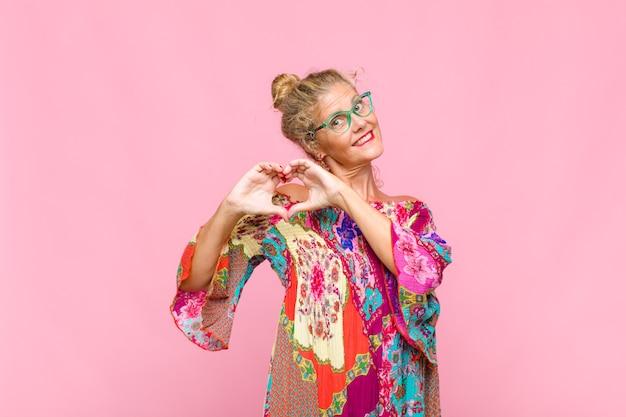 Женщина среднего возраста улыбается и чувствует себя счастливой, милой, романтичной и влюбленной, делая сердечко обеими руками