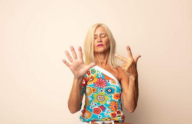 笑顔でフレンドリーに見える中年女性、前に手を前に8番または8番を示し、カウントダウン