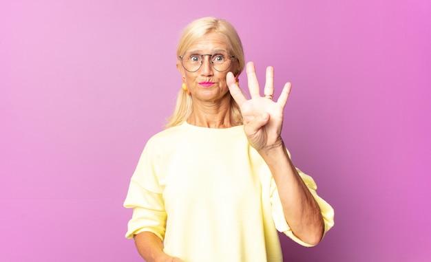 미소하고 친절하게 보이는 중년 여성, 앞으로 손으로 4 번 또는 4 번 표시, 카운트 다운