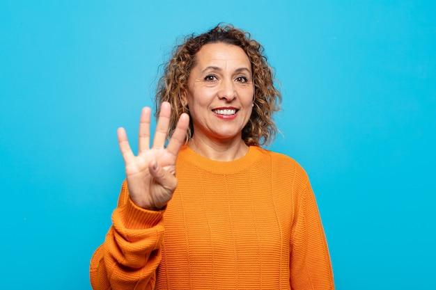 중년 여성이 웃고 친절하게보고, 앞으로 손으로 4 번 또는 4 번을 표시합니다.