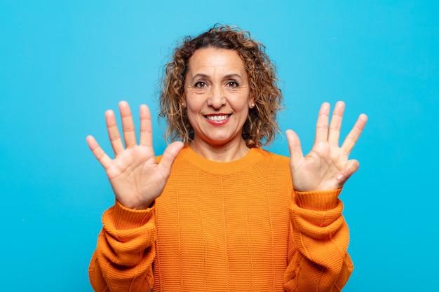 중년 여성이 미소하고 친절하게보고, 앞으로 손으로 번호 9 또는 9를 보여주는, 카운트 다운