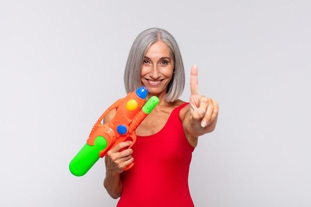 중년 여성이 웃고 친절하게보고, 손으로 넘버 원 또는 첫 번째를 보여주고, 물총으로 카운트 다운