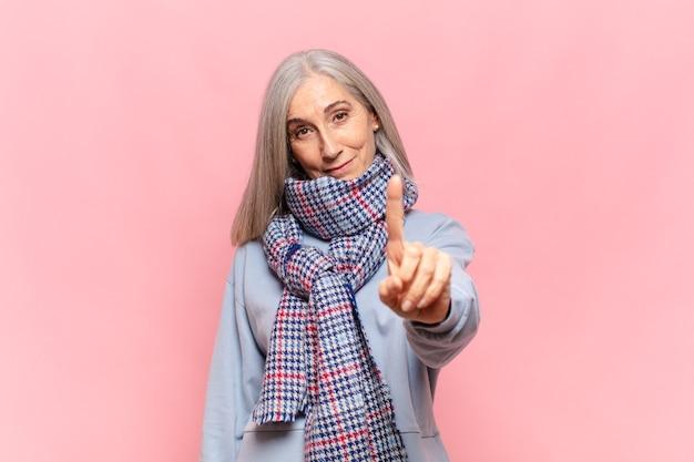 중년 여성이 미소하고 친절하게보고, 앞으로 손으로 번호 하나 또는 첫 번째 표시, 카운트 다운