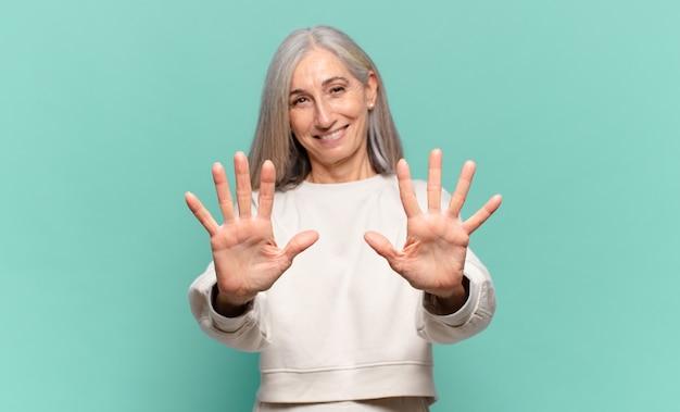 미소하고 친절하게 보이는 중년 여성, 앞으로 손으로 숫자 10 또는 10을 보여주는 카운트 다운