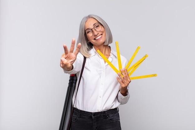 중간 나이 여자 웃 고 친절 하 게 찾고, 앞으로 손으로 3 번 또는 세 번째 표시, 카운트 다운. 건축가 개념