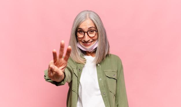 중년 여성이 미소하고 손으로 카운트 다운으로 세 번째 또는 세 번째를 보여주는 친절한 찾고