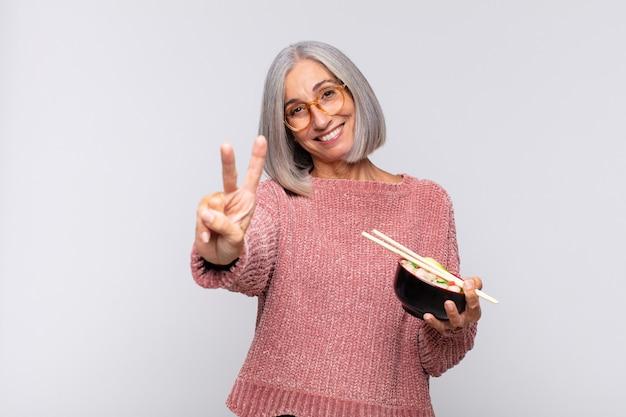 중간 나이 여자 웃 고 친절 하 게 찾고, 앞으로 손으로 2 번 또는 초를 표시, 아시아 음식 개념을 카운트 다운