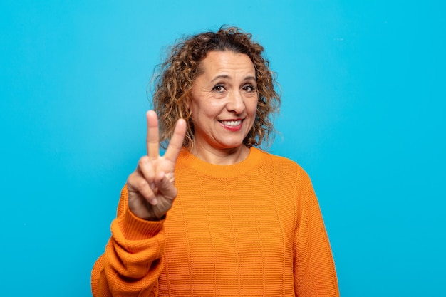 중년 여성이 미소하고 친절하게보고, 앞으로 손으로 2 번 또는 초를 표시하고, 카운트 다운