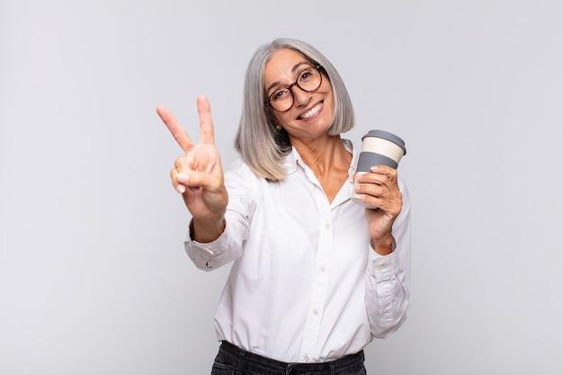 笑顔と幸せそうに見える中年女性、のんきで前向きな、片手コーヒーのコンセプトで勝利または平和を身振りで示す