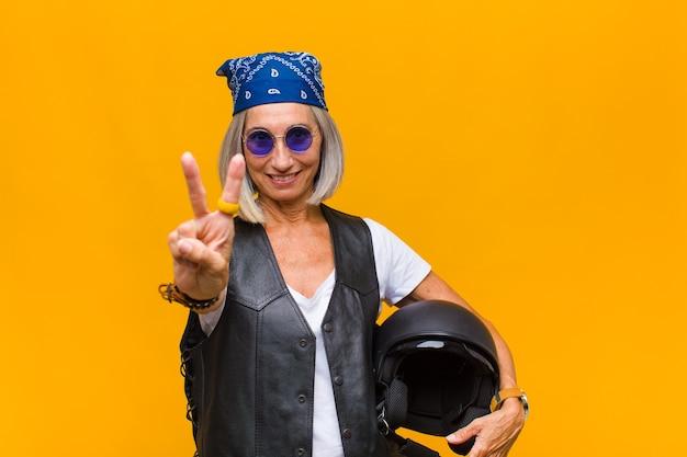 Женщина среднего возраста улыбается и выглядит счастливой, беззаботной и позитивной, жестикулируя победу или мир одной рукой