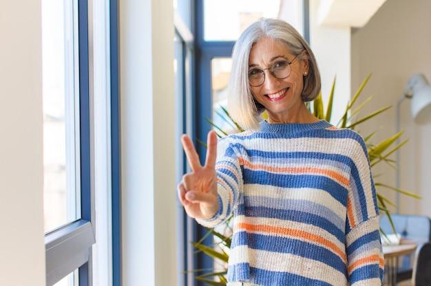 笑顔で幸せそうに見える中年女性、のんきで前向きで、片手で勝利や平和を身振りで示す