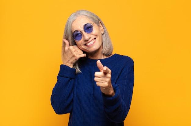 Женщина среднего возраста весело улыбается и показывает вперед, когда звонит вам позже жестом, разговаривает по телефону