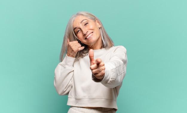 Женщина среднего возраста весело улыбается и указывает на камеру, звоня вам позже жестом, разговаривая по телефону