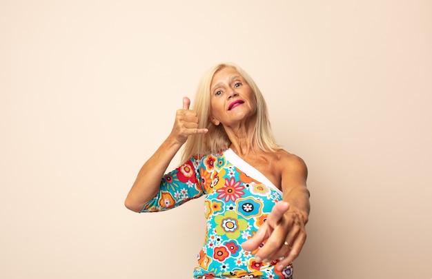 Женщина среднего возраста весело улыбается и указывает на камеру, звоня вам позже жестом