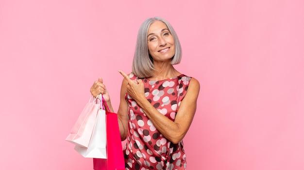陽気に笑う中年女性、幸せな気分で横や上を指す