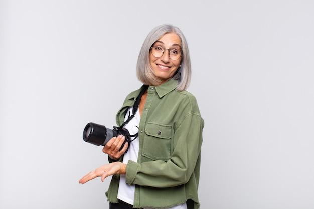 元気に笑って、幸せを感じて、手のひらでコピースペースでコンセプトを示す中年女性。写真家のコンセプト