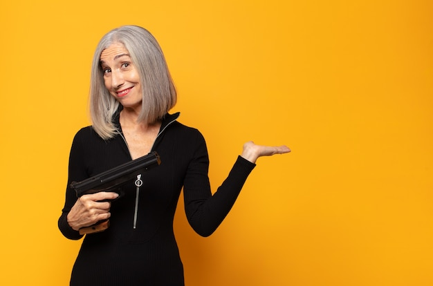 Middle age woman smiling cheerfully, feeling happy and showing a concept in copy space with palm of hand