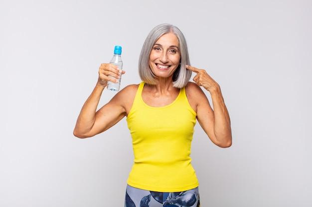 자신의 넓은 미소, 긍정적이고 편안하고 만족스러운 태도를 자신있게 가리키는 중년 여성. 피트니스 개념