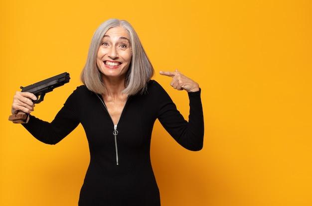 Женщина среднего возраста уверенно улыбается, указывая на собственную широкую улыбку, позитивное, расслабленное, удовлетворенное отношение