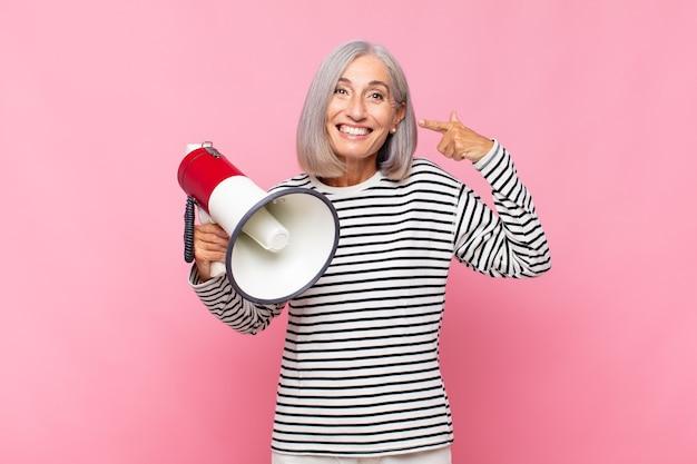 Женщина среднего возраста уверенно улыбается, указывая на собственную широкую улыбку