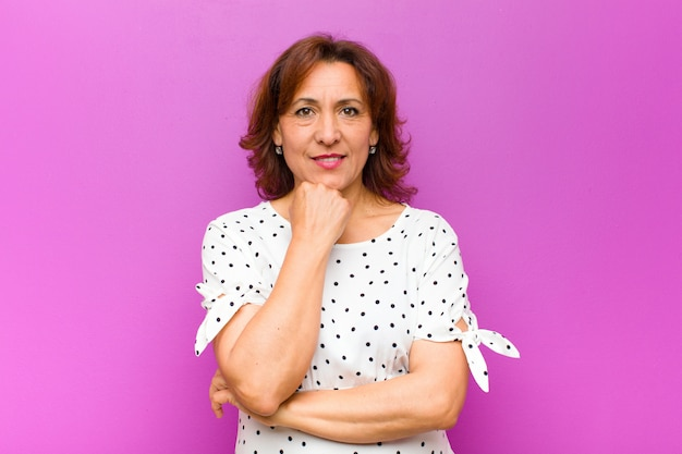 Middle age woman smiling, enjoying life, feeling happy, friendly, satisfied and carefree with hand on chin over purple wall