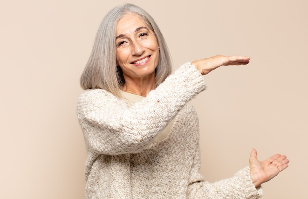 笑顔、幸せ、前向きで満足している、コピースペースでオブジェクトやコンセプトを保持または表示している中年女性