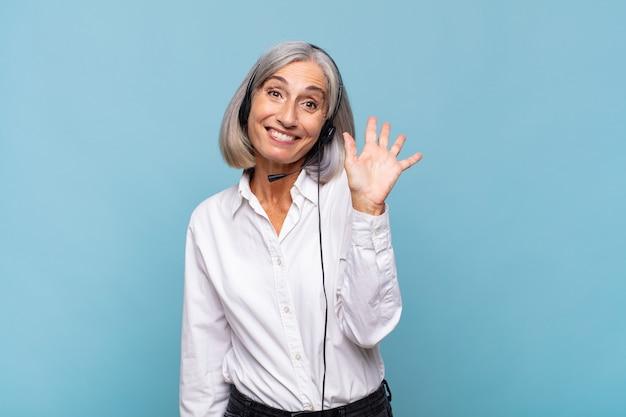 Женщина среднего возраста счастливо и весело улыбается, машет рукой, приветствует и приветствует вас или прощается. концепция телемаркетинга