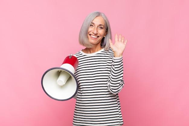 Женщина среднего возраста счастливо и весело улыбается, машет рукой, приветствует и приветствует вас или прощается с мегафоном
