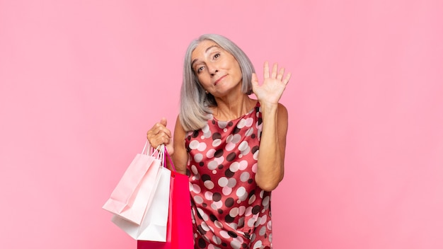 中年女性は、楽しく元気に笑ったり、手を振ったり、歓迎して挨拶したり、買い物袋で別れを告げたりします。