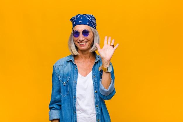 행복하고 유쾌하게 웃고, 손을 흔들며, 환영하고 인사하거나, 작별 인사를하는 중년 여성