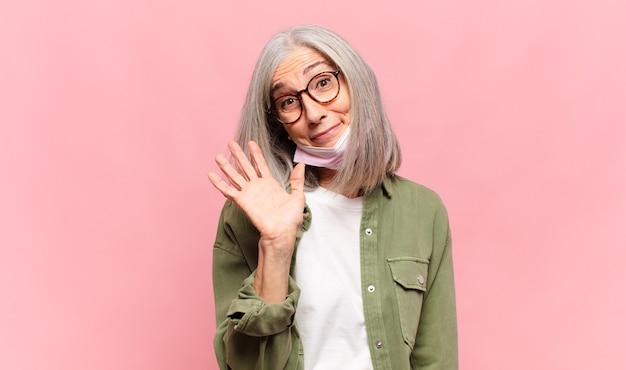中年女性は、楽しく元気に笑ったり、手を振ったり、歓迎して挨拶したり、さようならを言ったりします。