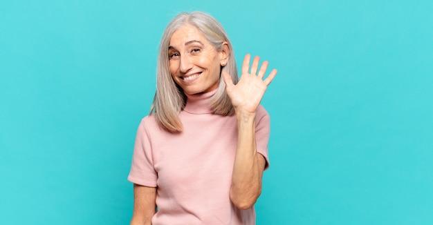 Женщина среднего возраста счастливо и весело улыбается, машет рукой, приветствует и приветствует вас или прощается