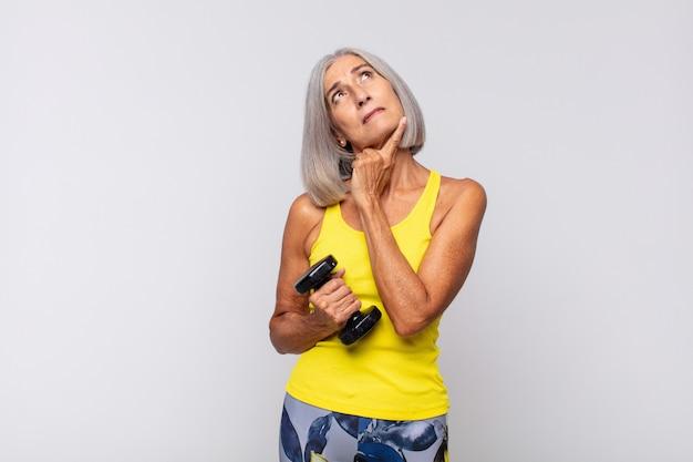 Женщина среднего возраста счастливо улыбается и мечтает или сомневается, глядя в сторону. фитнес-концепция