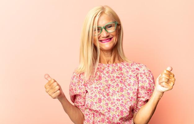 Женщина среднего возраста счастливо улыбается и показывает в сторону и вверх обеими руками, показывая объект в копировальном пространстве